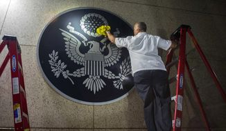 A worker wipes a representation of the The Great Seal of the United States at the the newly opened U.S. Embassy in Havana, Cuba, Friday, Aug. 14, 2015. U.S. Secretary of State John Kerry arrived Friday morning in Havana for an historic ceremony to raise the U.S. flag over the restored U.S. Embassy in the Cuban capital. (AP Photo/Ramon Espinosa)