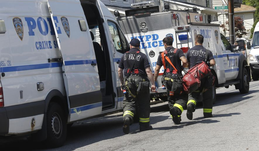 New York City firefighters carry their gear near the scene of a standoff, Friday, Aug. 14, 2015, in the Staten Island borough of New York. Garland Tyree, a high-ranking member of the Bloods street gang who was to be arrested on parole violations when he shot a firefighter responding to a call of smoke coming from his girlfriend's home, died Friday in a gunfight with police after a six-hour standoff, two police officials said.  (AP Photo/Mary Altaffer)