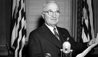 Wearing the same stern expression that characterized his press conference appearance, President Harry S. Truman repeats for cameramen (who were excluded at the news session) his warning that U.N. forces would not back down in Korea and the atom bomb would be used if necessary to meet the military situation. The re-enactment was in the same executive office room in Washington, Nov. 30, 1950 where his press conferences are held. (AP Photo/Henry Griffin)