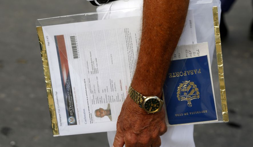 A man applying for a U.S. visa holds his U.S. Department of State forms and Cuban passport as he waits in line outside the U.S. Interests Section in Havana on July 1, 2015. (Associated Press) **FILE**