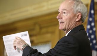 Arkansas Gov. Asa Hutchinson points out details on a Medicaid form at the Arkansas state Capitol in Little Rock, Ark., Tuesday, Aug. 4, 2015. (AP Photo/Danny Johnston)