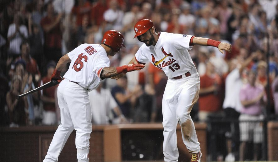 St. Louis Cardinals' Matt Carpenter (13) Is congratulated by Kolten Wong (16) after his solo home run against the Miami Marlins during the eighth inning of a baseball game, Friday, Aug. 14, 2015, at Busch Stadium in St. Louis. (AP Photo/Bill Boyce)