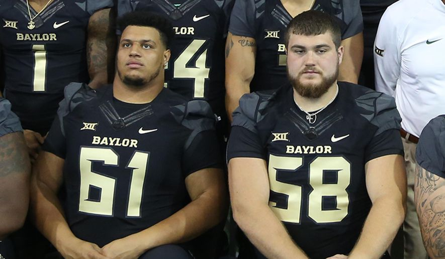 Baylor seniors Jarell Broxton (61) and Spencer Drango (58) line up with other members of the NCA college football for a team photo, Thursday, Aug. 13, 2015, in Waco, Texas. The numbers on the two players' jerseys reflect the score of last year's game with TCU which Baylor won. (Rod Aydelotte/Waco Tribune Herald, via AP)