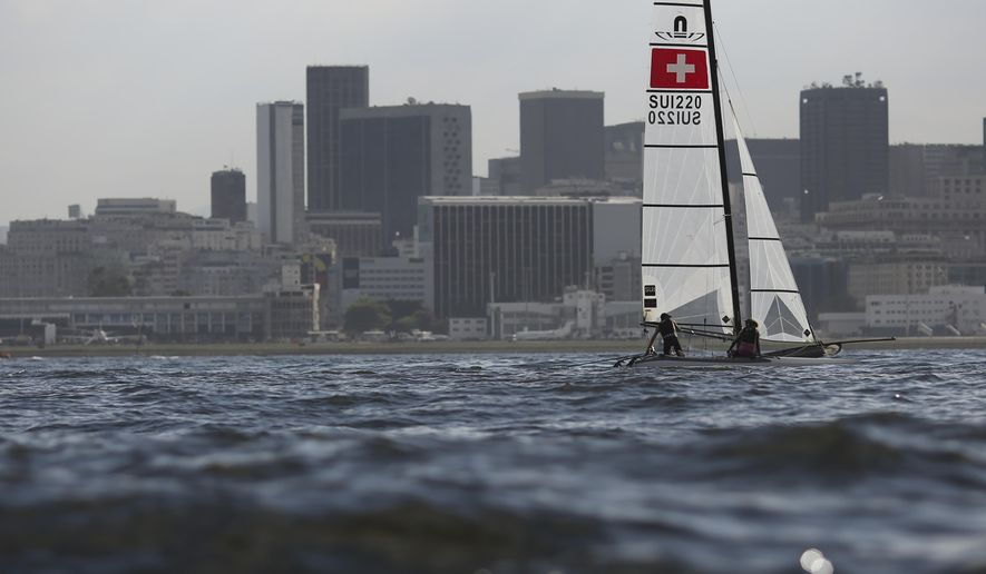 "Athletes Nathalie Brugger, right, and Matias Buhler, from Switerzland, of the Nacra 17 class, practice a day before the sailing test event ahead of the Rio 2016 Olympic Games in Guanabara Bay in Rio de Janeiro, Brazil, Friday, Aug. 14, 2015. Bruce Gordon, the WHO's coordinator of water, sanitation, hygiene and health, said that testing for viruses ""would be advisable"" given it's known that human sewage pollution is rife in Rio's waters. (AP Photo/Leo Correa)"