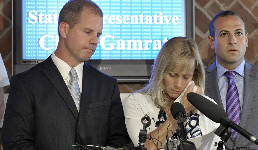Michigan Rep. Cindy Gamrat, R-Plainwell, wipes away tears as she holds a brief news conference at the Abood Law Firm in East Lansing, Mich., on Friday Aug 14, 2015.   The embattled but apologetic Michigan lawmaker who had an extramarital affair with another married legislator said Friday she will not resign from office for now and denied any role in a bizarre, fictional email sent to deflect attention from their relationship.  (Dale G. Young, Detroit News via AP)