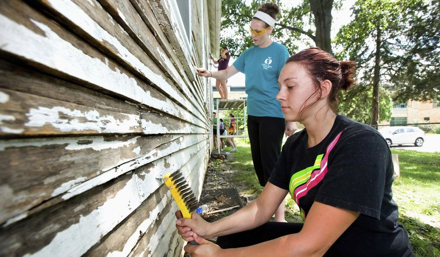 In this June 29, 2015, photo, Golden Apple Scholars Jeana Craft, right, and Hannah Leib work with other participants in the program to scrape paint from the siding of Greenwood School House in Charleston, Ill. The Golden Apple Scholars were on Eastern Illinois University's campus through July 18 for their annual summer program. The organization is comprised of college students studying education. (Kevin Kilhoffer/Times-Courier via AP)