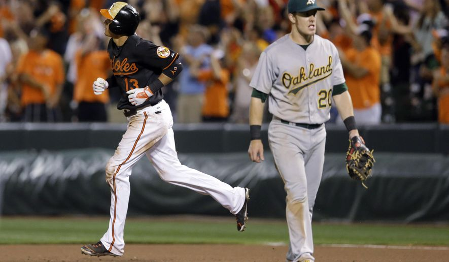 Baltimore Orioles' Manny Machado, left, rounds the bases past Oakland Athletics first baseman Mark Canha after hitting a two-run home run to end a baseball game, Friday, Aug. 14, 2015, in Baltimore. Baltimore won 8-6 in 13 innings. (AP Photo/Patrick Semansky)