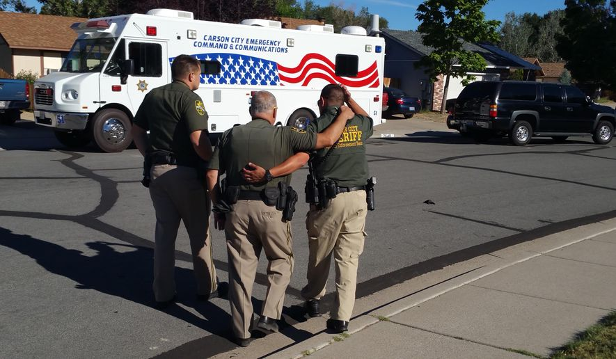 Carson City Sherrif's Department deputies comfort each other outside the scene of a fatal shooting Saturday, Aug. 15, 2015, in Carson City, Nev., that left an officer and a suspect dead. Officials say a Nevada sheriff's deputy is dead after a suspect opened fire on officers responding to a domestic violence call. Authorities say the suspect was later found dead at the scene of the confrontation, which happened a little after 2 a.m. Saturday in East Carson City. (AP Photo/Michelle Rindels) (AP Photo/Michelle Rindels)