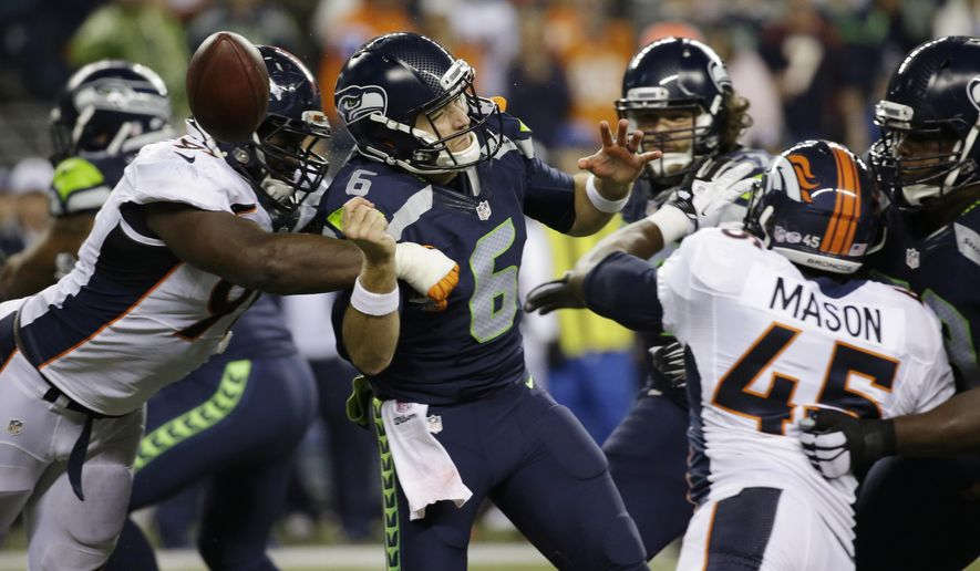 Denver Broncos defensive end Kenny Anunike, left, sacks Seattle Seahawks quarterback R.J. Archer (6) and causes him to fumble the ball out of bounds during the second half of a preseason NFL football game, Friday, Aug. 14, 2015, in Seattle. (AP Photo/Elaine Thompson)