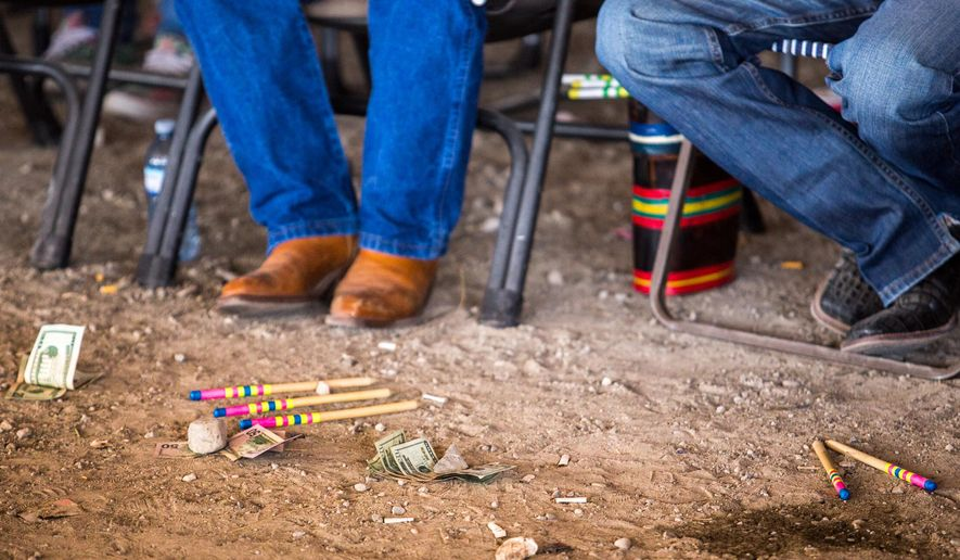 "In this photo taken Saturday, Aug. 8, 2015, bets lay on the ground next to counting sticks during the Pat ""Bum"" Boss Ribs Sr. memorial stick game tournament in Heart Butte, Mont. Stick game is older than recorded history, yet it remains largely unknown to people outside Native American culture. Its rules are deceptively simple, but demand a player remain intently focused; sometimes for hours at a time. (Evan Frost/The Great Falls Tribune via AP)  NO SALES; MANDATORY CREDIT"
