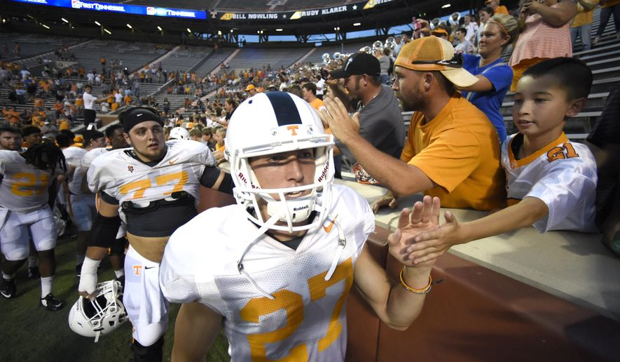 Tennessee punter Tommy Townsend (27) high fives a young fan at the end of Tennessee's open football practice at Neyland Stadium on Saturday, Aug. 15, 2015 in Knoxville, Tenn.. (Adam Lau/Knoxville News Sentinel via AP) MANDATORY CREDIT