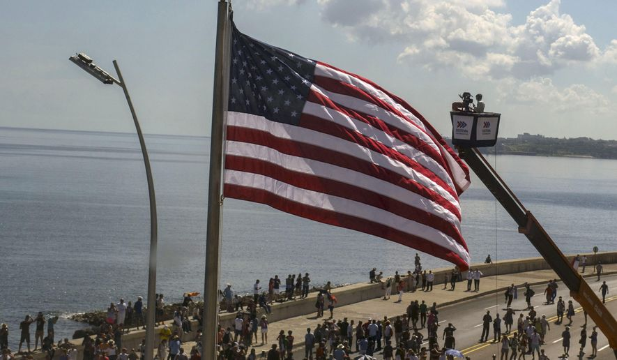 In this photo taken through a window, Cuban videographers film the U.S. flag from a crane after it was raised at the U.S. Embassy in Havana, Friday, Aug. 14, 2015. The Stars and Stripes rose over the newly reopened U.S. Embassy after a half-century of broken diplomatic relations. (AP Photo/Ramon Espinosa)