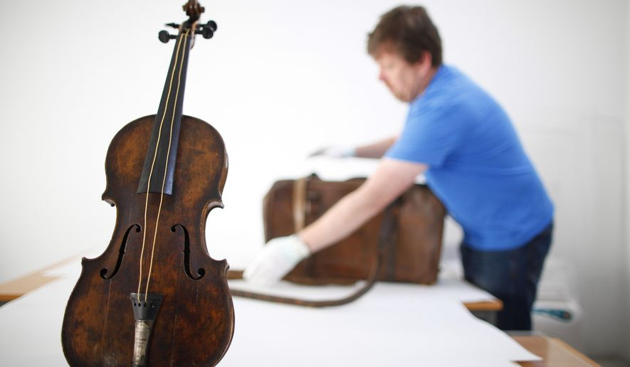 FILE - In this Sept. 16, 2013 file photo, Sean Madden, of Fine Art Conservation, works to show the violin played by bandmaster Wallace Hartley during Titanic's tragic maiden voyage, during a photocall to the media in Lurgan, Northern Ireland. The sea-corroded violin believed to have been played by the bandmaster of the Titanic as the ocean liner sank will be displayed next year at a pair of U.S. museums; from March 7 to May 29 in Branson, Missouri, and from June 5 to Aug. 14 in Pigeon Forge, Tennessee.  (AP Photo/Peter Morrison, File)