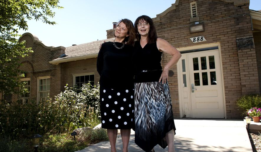 In this July 28, 2015 photo, Shayne Madsen, left, stands with her long-lost sister, Diane Lippoldt-Johnson, right, in front of what was once an orphanage in Denver.     (Ryan Gooding/Daily Camera via AP) NO SALES; MANDATORY CREDIT