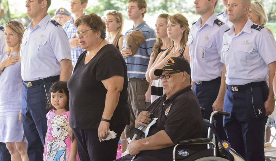ADVANCE FOR USE SUNDAY, AUG. 16, 2015 AND THEREAFTER - In this Aug. 8, 2015 photo, residents and military personnel attend a memorial service in honor of 45 victims of the Chagui'an Massacre in Yigo, Guam. The massacre happened in WWII during the 1944 liberation of the island. U.S. Marine patrols from the 21st Regiment discovered 45 bodies of Chamorro men in Chagui'an. The victims had been beheaded and had their hands tied behind their backs. A white cross symbolizes the 45 men who were found at the site, while signs list their names and a short story about the site in English, Chamorro and Japanese. (Mark Scott/Pacific Daily News via AP) ALL GUAM, MICRONESIA MEDIA OUT, MANDATORY CREDIT