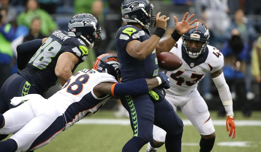 Seattle Seahawks quarterback Russell Wilson has the football stripped by outside linebacker Von Miller, lower left, for a fumble in the first half of a preseason NFL football game, Friday, Aug. 14, 2015, in Seattle. Denver recovered the ball. (AP Photo/Elaine Thompson)