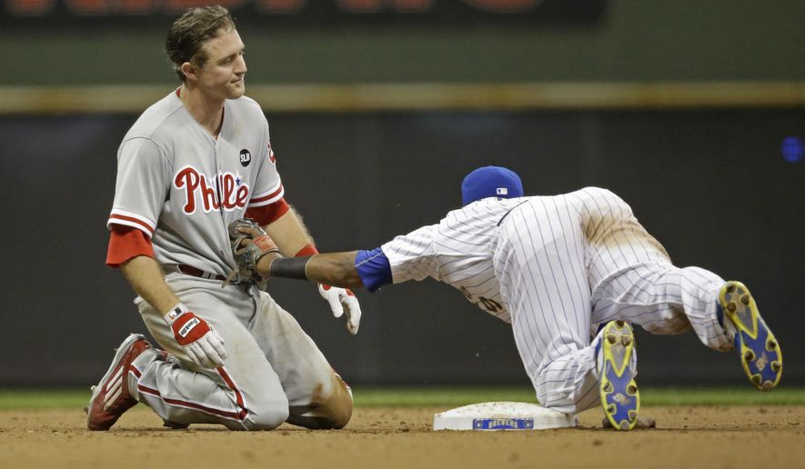 Milwaukee Brewers' Jean Segura, right,  dives to tag out Philadelphia Phillies' Chase Utley, left, who over slid second base during the seventh inning of a baseball game Friday, Aug. 14, 2015, in Milwaukee. (AP Photo/Jeffrey Phelps)