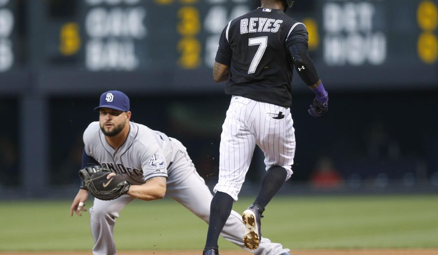 San Diego Padres first baseman Yonder Alonso, left, fields the throw to put out Colorado Rockies' Jose Reyes after his sacrifice bunt to advance base runner Charlie Blackmon from second to third base in the first inning of a baseball game Saturday, Aug. 15, 2015, in Denver. (AP Photo/David Zalubowski)
