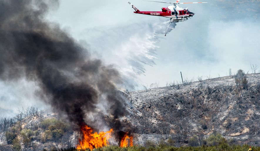 A helicopter makes a water drop on a wildfire in Angeles National Forest above Azusa, Calif., Friday, Aug. 14, 2015. Wildfires racing through drought-stricken Southern California have burned hundreds of acres of land and multiple cabins as the region roasted under a summer heat wave. (Watchara Phomicinda/San Gabriel Valley Tribune via AP) MAGS OUT; NO SALES; MANDATORY CREDIT