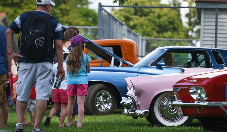 People look at classic cars parked in Memorial Park during the Woodward Dream Cruise, Friday, Aug. 14, 2015, in Royal Oak, Mich. (Tanya Moutzalias/The Ann Arbor News-MLive.com Detroit via AP) LOCAL TELEVISION OUT; LOCAL INTERNET OUT; MANDATORY CREDIT