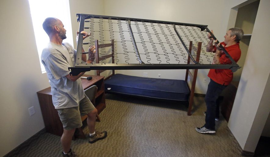 This Friday, Aug. 7, 2015, shows Southern Utah University's Brad Niederhauser, Building Repairs & Renovations Supervisor, left, and Chris Ralphs, Director of University Housing, building a bunk bed in Cedar Hall South on the campus of Southern Utah University, in Cedar City, Utah. This fall, an enrollment boom that created a housing crisis is prompting Southern Utah University to urge neighbors and employees alike to house the dormless, including hundreds of incoming freshmen who wanted to live on campus. (AP Photo/Rick Bowmer)