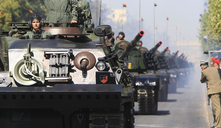 Polish army soldiers salute as tanks roll on one of the city's main streets during a military parade celebrating the Polish Army Day in Warsaw, Poland, Saturday, Aug. 15, 2015. (AP Photo/Czarek Sokolowski)