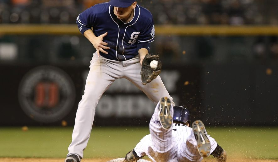 San Diego Padres shortstop Clint Barmes, left, fields the throw as Colorado Rockies' Brandon Barnes steals second base during the eighth inning of a baseball game Friday, Aug. 14, 2015, in Denver. San Diego won 9-5. (AP Photo/David Zalubowski)
