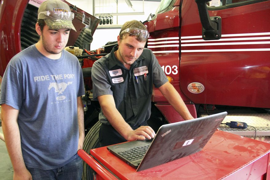 ADVANCE FOR WEEKEND EDITIONS AUG. 15-16 - In this Aug. 4, 2015 photo, York High student Ethan Thorne and Truck Center Companies' service manager Joel Kaup demonstrate what a modern diesel technician's workday looks like on most days in York, Neb. (Steve Moseley/The York News-Times via AP) MANDATORY CREDIT
