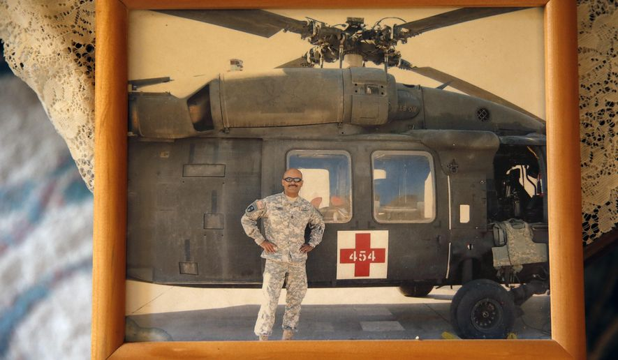 This March 17, 2015 photo shows a photgraph of now-retired U.S. Army Sgt. 1st Class Marshall Powell standing with a U.S. Army MEDEVAC helicopter in Iraq during his last tour to the country, at Powell's brother's house in Crescent, Okla. Powell, who served as a military nurse in Iraq and Afghanistan, was deeply haunted by his experiences, and nearly lost his own internal war with depression before finding meaningful help. (AP Photo/Brennan Linsley)
