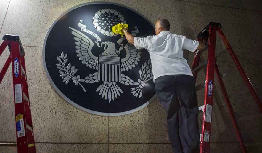 A worker wipes a representation of the The Great Seal of the United States at the newly opened U.S. Embassy in Havana, Cuba. (AP Photo/Ramon Espinosa)