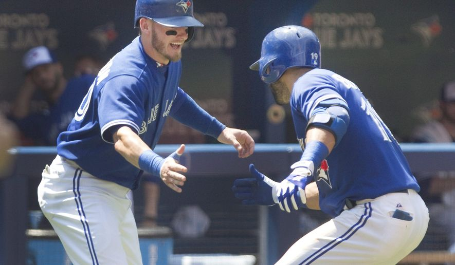 Toronto Blue Jays' Jose Bautista, right, is met by teammate Josh Donaldson after hitting two-run home run against the New York Yankees in the third inning of a baseball game in Toronto, Sunday, Aug. 16, 2015. (Fred Thornhill/The Canadian Press via AP) MANDATORY CREDIT