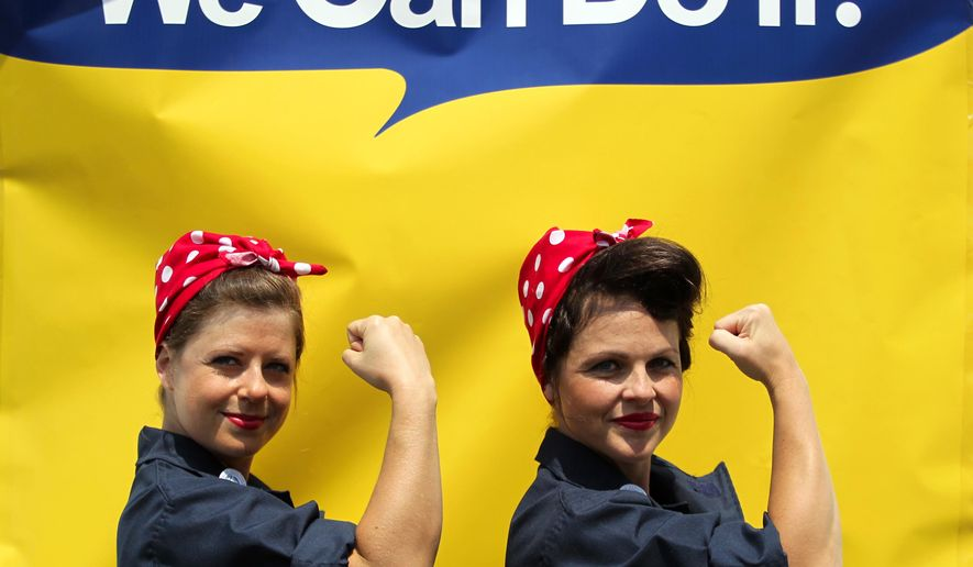 "Jessica Curtis, of Long Beach, Calif., and Sarah Neller, of Vacaville, Calif., pose for a photograph in front of a ""We Can Do It"" backdrop as they joined with hundreds of women dressed as ""Rosie the Riveter"" in an attempt to set a new Guinness World Record at Rosie the Riveter/WWII Home Front National Historical Park in Richmond, Calif., Saturday, Aug. 15, 2015. The current record was set last year when 776 Rosie and Rosie lookalikes gathered at the Willow Run Airport in Ypsilanti, Mich.  (Anda Chu/The Contra Costa Times via AP)"