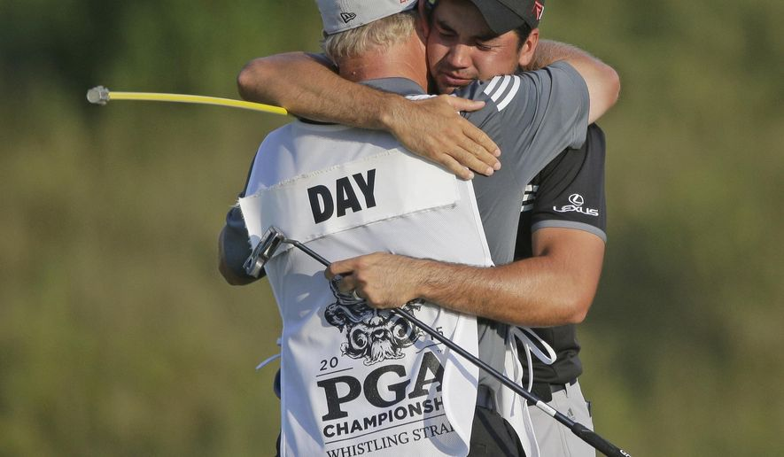Jason Day, of Australia, hugs his caddie Colin Swatton after winning the PGA Championship golf tournament Sunday, Aug. 16, 2015, at Whistling Straits in Haven, Wis.  (AP Photo/Jae Hong)