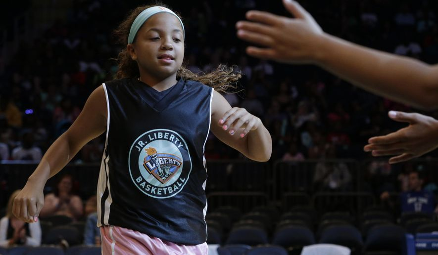 Kymora Johnson, of the Charlottesville Cavaliers, high-fives her teammates as she arrives on the court for an exhibition basketball game against Mount Vernon Recreation, Saturday, Aug. 15, 2015, at Madison Square Garden in New York. The 10-year-old girl was thrown into the spotlight earlier this month when her youth team from Virginia was disqualified from a basketball tournament because she played in it. Johnson's the lone girl on the boys' team, the Charlottesville Cavaliers. (AP Photo/Mary Altaffer)