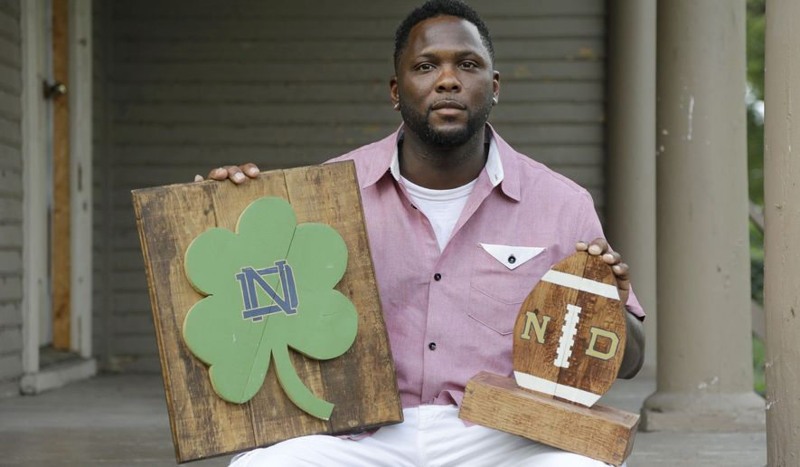 In this Aug. 14, 2015 photo, Larry Stephney holds wooden products he helped make while he was an inmate at a privately run prison in Nashville, Tenn. Stephney says inmates were required to build plaques, birdhouses, dog beds and cornhole games for officials who sold the items through an online business and at a local flea market. (AP Photo/Mark Humphrey)