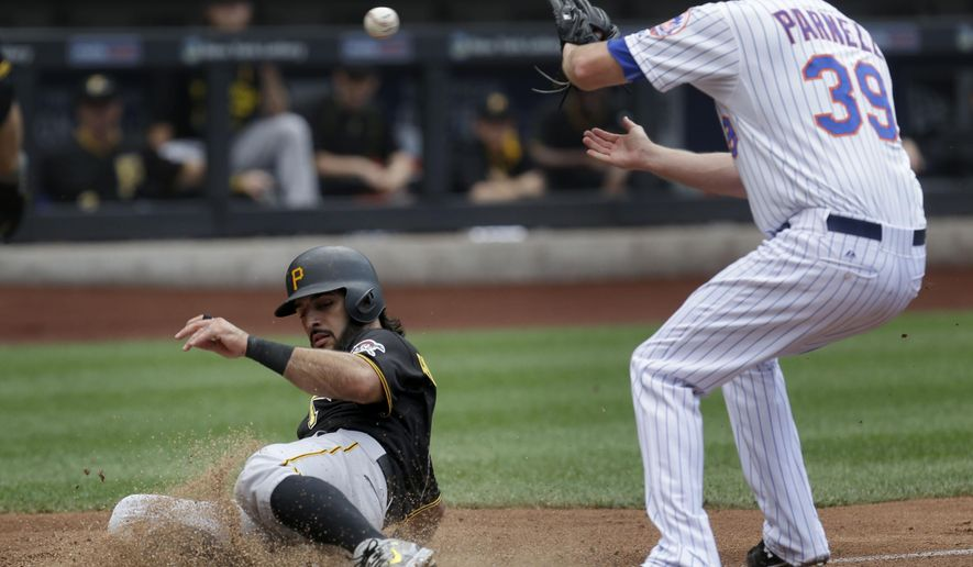 Pittsburgh Pirates' Sean Rodriguez, left, scores past New York Mets relief pitcher Bobby Parnell on a passed ball during the seventh inning of the baseball game at Citi Field, Sunday, Aug. 16, 2015, in New York. (AP Photo/Seth Wenig)