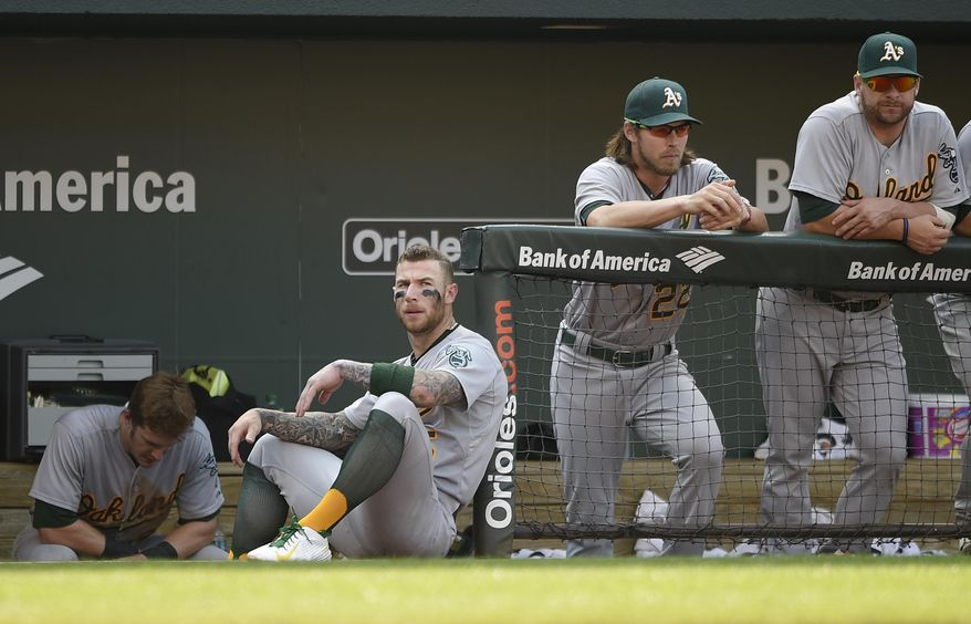 Oakland Athletics' Brett Lawrie, third from right, looks on from the dugout with Josh Reddick, second from right, and Stephen Vogt, right, during the ninth inning of a baseball game against the Baltimore Orioles, Sunday, Aug. 16, 2015, in Baltimore. The Orioles won 18-2. (AP Photo/Nick Wass)