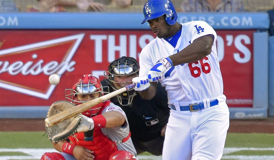 Los Angeles Dodgers' Yasiel Puig, right, hits a solo home run as Cincinnati Reds catcher Brayan Pena, left, and home plate umpire Dana DeMuth watch during the second inning of a baseball game, Saturday, Aug. 15, 2015, in Los Angeles. (AP Photo/Mark J. Terrill)