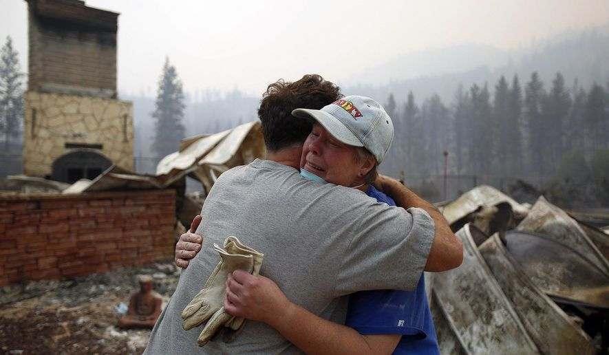 Cindy Aston hugs her neighbor, Todd Quinn, after she lost her childhood home in the neighborhood of Antoine Creek outside of Chelan, Wash. from the firestorm on Saturday, Aug. 15, 2015.  (Sy Bean/The Seattle Times via AP)