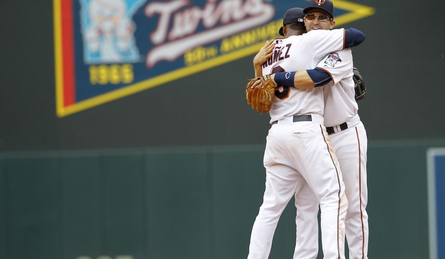 Minnesota Twins second baseman Brian Dozier, right, hugs shortstop Eduardo Nunez after the Twins defeated the Cleveland Indians 4-1 in a baseball game in Minneapolis, Sunday, Aug. 16, 2015.  (AP Photo/Ann Heisenfelt)