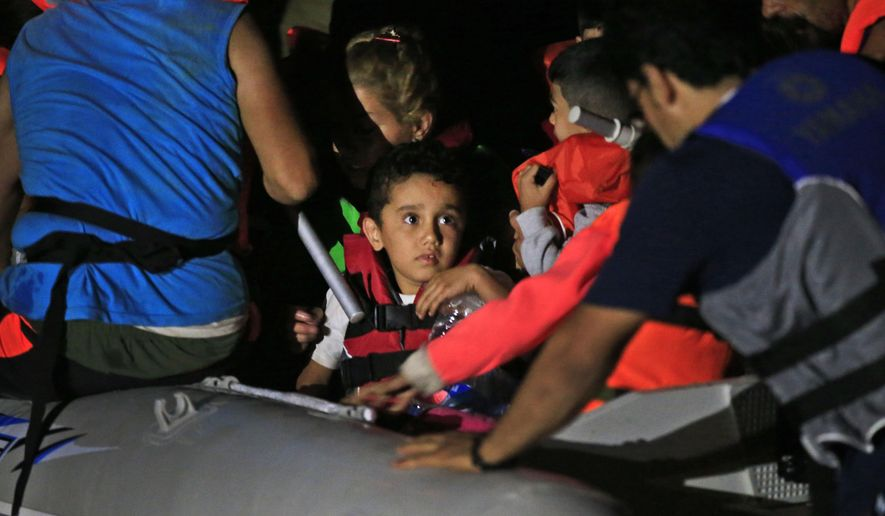 Migrants mostly from Iran, including children, start their journey on a dinghy from the coastal town of Bodrum, Turkey, to the nearby Greek island of Kos, early Sunday, Aug. 16, 2015. With the shores of Kos - a gateway to Europe - just a few kilometers (miles) away, hundreds of migrants are piling into tiny inflatable dinghies each night and attempting to make the crossing powered by tiny outboard motors and plastic paddles. (AP Photo/Lefteris Pitarakis)