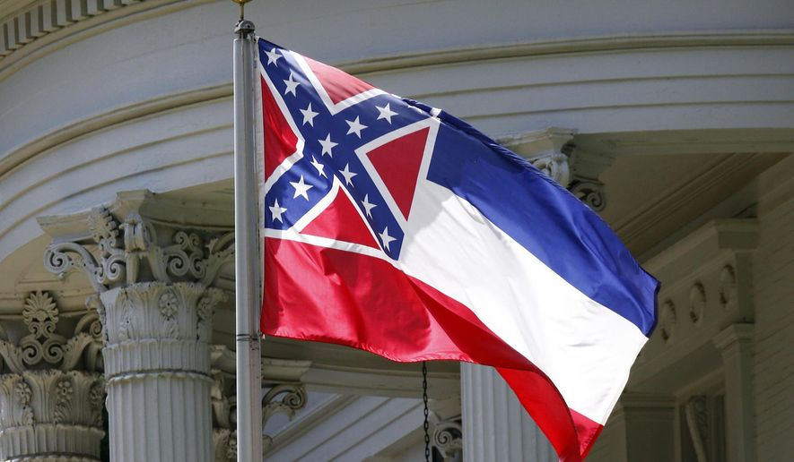 FILE - In this June 23, 2015, file photograph, the state flag of Mississippi is unfurled against the front of the Governor's Mansion in Jackson, Miss. Jimmy Buffet, John Grisham, Morgan Freeman and former New Orleans Saints quarterback Archie Manning are among many famous current and former Mississippi residents asking the state to remove the Confederate battle emblem from its flag. (AP Photo/Rogelio V. Solis, File)