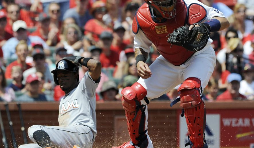 St. Louis Cardinals' Yadier Molina, right, waits for the throw as Miami Marlins' Dee Gordon scores on an RBI-single by Justin Bour in the first inning of a baseball game, Sunday, Aug. 16, 2015, at Busch Stadium in St. Louis. (AP Photo/Bill Boyce)