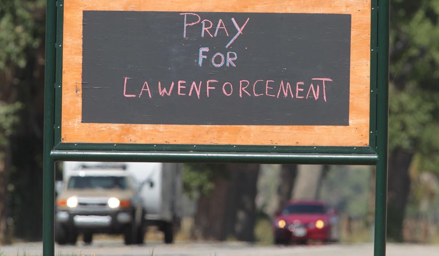A sign stating to pray for law enforcement is visible to motorists in Weldon, Calif., next to the Weldon Methodist Church, off Highway 178, Saturday, Aug. 15, 2015. Sheriff's deputies in California said that they have shot and killed a man believed to be the target of a 2-week-long manhunt in the rugged, mountainous high desert of Central California on Saturday, Aug. 15, 2015. Dozens of officers have been searching in remote terrain about 30 miles east of Bakersfield, Calif., for Benjamin Peter Ashley. (Casey Christie/The Bakersfield Californian via AP)  MANDATORY CREDIT; MAGS OUT; NO SALES; ONLINE OUT; TV OUT