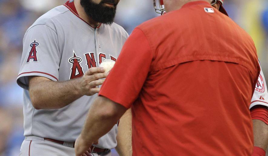 Los Angeles Angels starting pitcher Matt Shoemaker, left, hands the ball to manager Mike Scioscia during the second inning of a baseball game against the Kansas City Royals at Kauffman Stadium in Kansas City, Mo., Saturday, Aug. 15, 2015. The Royals scored six runs in the inning. (AP Photo/Orlin Wagner)