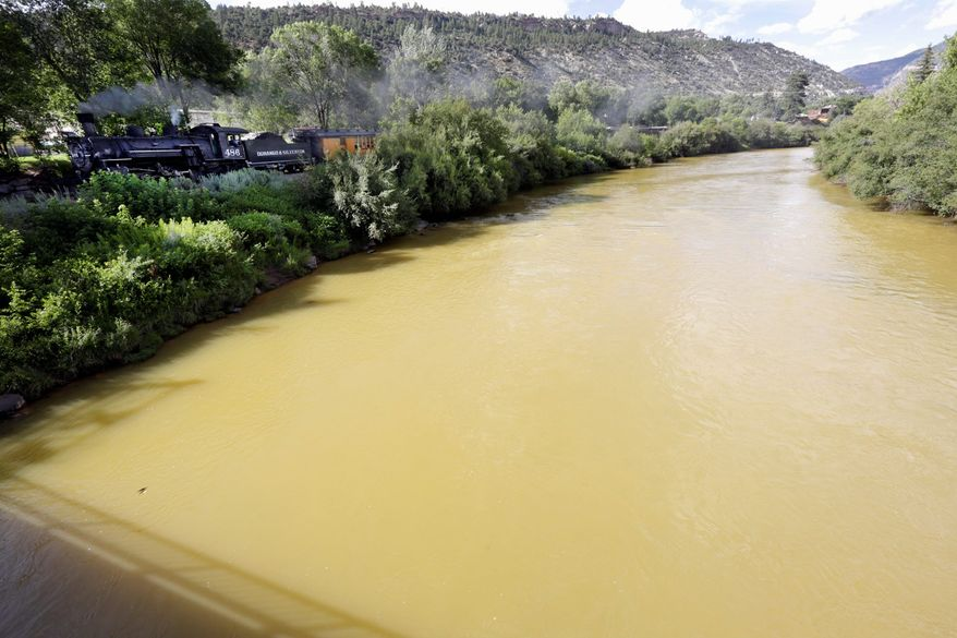 The Animas River flows with toxic waste from the Gold King Mine on Aug. 8, 2015, as seen from the 32nd Street Bridge in Durango, Colo., as the Durango & Silverton Narrow Gauge Railroad train goes by. (Associated Press) **FILE**