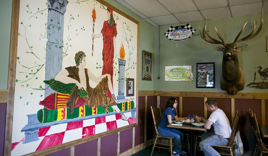 In this photo taken Sunday, Aug. 9, 2015, Glynis Frederiksen and Brian Campbell of Seattle have lunch in the light of a mural painted by local boy makes good, Chris Pratt, at Omega Pizza and Pasta in Granite Falls, Wash. Pratt, best friends with the owner's son, has been known to tie on an apron and help out in the kitchen on one his recent visits. (Kevin Clark/The Herald via AP) MANDATORY CREDIT