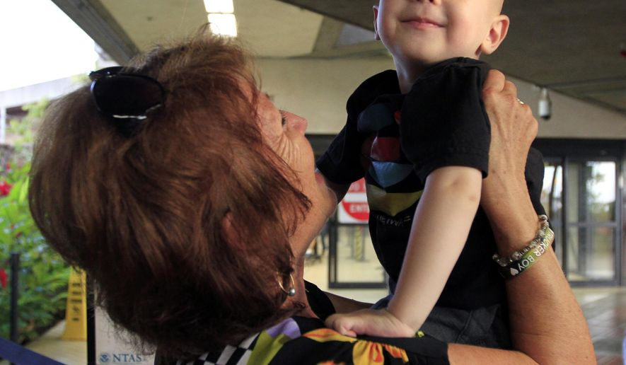 ADVANCE FOR SUNDAY AUG. 16 AND THEREAFTER - In this Thursday Aug. 6, 2015, photo, two-year-old Trucker Dukes is held by his grandmother Judy Stratford as he arrives at Kahului Airport in Kahului, Hawaii, as he returning from New York from after nearly nine months undergoing cancer treatment. (Chris Sugidono/The News via AP) MANDATORY CREDIT
