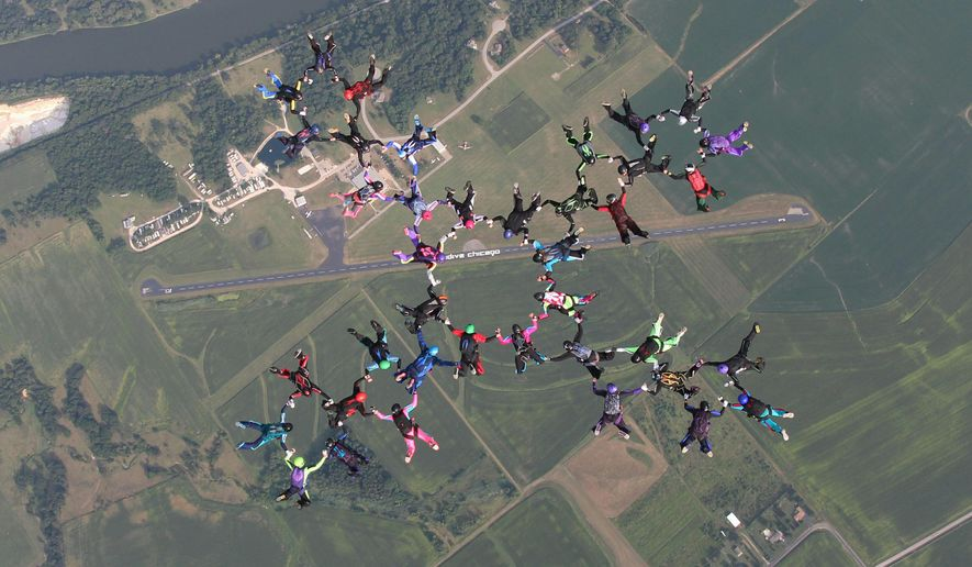 In a Saturday, Aug. 15, 2015 photo provided by Henrik Csuri, 39 women skydivers from around the country jump from two planes to build a cross-shaped belly formation and set a state skydiving record over Skydive Chicago in Ottawa, 80 miles southwest of Chicago. The skydivers topped the previous record of 35 women set in August 2013. The national record is 182 women. (Henrik Csuri via AP)