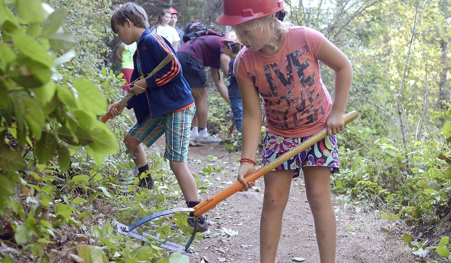 In this photo taken Aug. 7, 2015, Cyleigh Howard, 8, joins other campers helping to improve the Blanchard Mountain trail near the Samish Overlook in Burlington, Wash. Experience The Wild is a free day camp for 8- to 12-year-olds. It is sponsored by the Pacific Northwest Trail Association (PNTA) and the U.S. Forest Service. (Scott Terrell/The Skagit Valley Herald via AP) MANDATORY CREDIT